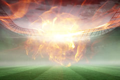 Composite image of ball of fire 3d. Ball of fire against misty football stadium under floodlights 3d Royalty Free Stock Image