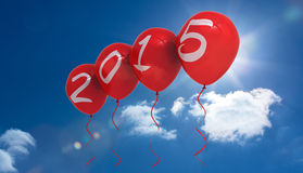 Composite image of 2015 balloons. 2015 balloons against bright blue sky with clouds Stock Photo