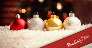 Composite image of banner sending love. Banner sending love against multi colored christmas baubles lined up Stock Image