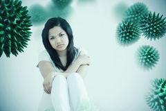 Composite image of barefoot woman sitting on the floor. Barefoot woman sitting on the floor against white background with vignette stock photo
