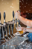 Composite image of barman pulling a pint of beer Royalty Free Stock Photos