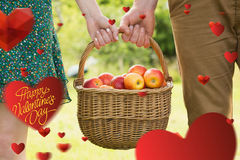 Composite image of basket of apples being carried by a young couple. Basket of apples being carried by a young couple against happy valentines day stock photo