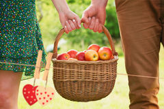 Composite image of basket of apples being carried by a young couple. Basket of apples being carried by a young couple against hearts hanging on the line Stock Images