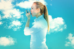 Composite image of beautiful blonde using an asthma inhaler Stock Image