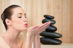 Composite image of beautiful brunette blowing over hands. Beautiful brunette blowing over hands against stack of smooth balancing rocks Royalty Free Stock Photos