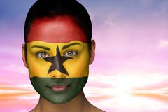 Composite image of beautiful brunette in ghana facepaint Royalty Free Stock Images