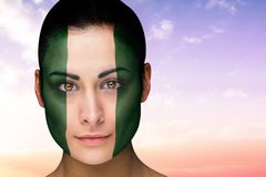 Composite image of beautiful brunette in nigeria facepaint Royalty Free Stock Photos