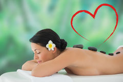 Composite image of beautiful brunette relaxing on massage table Stock Photography