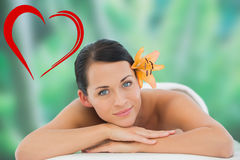Composite image of beautiful brunette relaxing on massage table smiling at camera Royalty Free Stock Photo