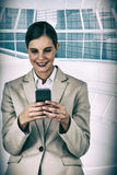 Composite image of beautiful businesswoman using mobile phone Stock Images
