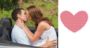 Composite image of beautiful couple kissing in back seat Stock Image