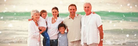 Composite image of beautiful family at the beach. Beautiful family at the beach against snow falling stock photography