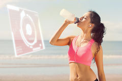 Composite image of beautiful healthy woman drinking water on beach royalty free stock photos