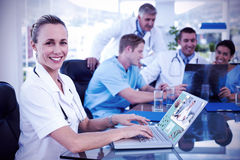 Composite image of beautiful smiling doctor typing on keyboard with her team behind. Beautiful smiling doctor typing on keyboard with her team behind against Royalty Free Stock Photo
