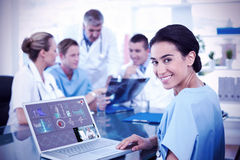 Composite image of beautiful smiling doctor typing on keyboard with her team behind stock photo