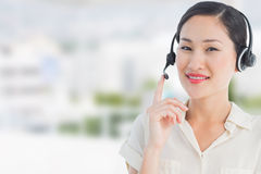 Composite image of beautiful smiling female executive with headset Stock Photo