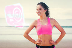 Composite image of beautiful smiling healthy with earphones on beach Stock Image