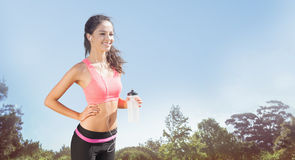 Composite image of beautiful smiling healthy woman holding water bottle stock photo