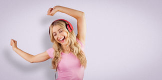Composite image of beautiful woman dancing with headphones Stock Photography