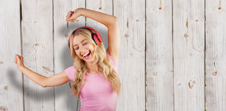 Composite image of beautiful woman dancing with headphones Stock Photos