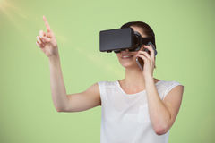 Composite image of beautiful woman gesturing while suing virtual reality headset and talking mobile Royalty Free Stock Images