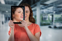 Composite image of beautiful woman holding digital tablet in front of her face. Beautiful woman holding digital tablet in front of her face against classroom stock image