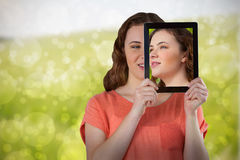 Composite image of beautiful woman holding digital tablet in front of her face. Beautiful woman holding digital tablet in front of her face against green meadow stock photos