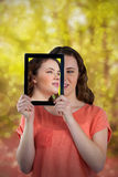 Composite image of beautiful woman holding digital tablet in front of her face. Beautiful woman holding digital tablet in front of her face against peaceful royalty free stock image