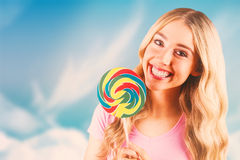 Composite image of a beautiful woman holding a giant lollipop Stock Image
