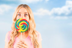 Composite image of a beautiful woman holding a giant lollipop Stock Images