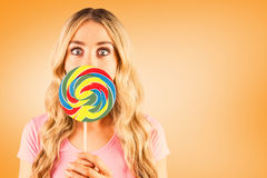 Composite image of a beautiful woman holding a giant lollipop Royalty Free Stock Images