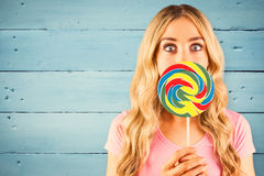 Composite image of a beautiful woman holding a giant lollipop Royalty Free Stock Photos