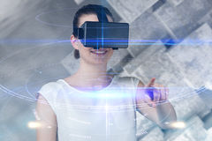 Composite image of beautiful woman imagining with virtual reality headset. Beautiful woman imagining with virtual reality headset  against futuristic black Stock Photo