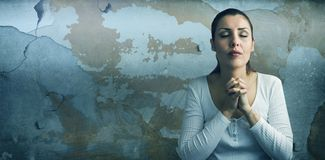 Composite image of beautiful woman praying with joining hands and eyes closed. Beautiful woman praying with joining hands and eyes closed against rusty weathered stock photo