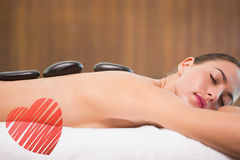 Composite image of beautiful woman receiving stone massage at health farm Stock Photography