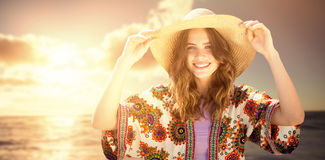 Composite image of beautiful woman with a straw hat. Beautiful woman with a straw hat  against view of beautiful sea Stock Photo