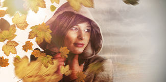 Composite image of beautiful woman wearing winter coat looking away Royalty Free Stock Photos