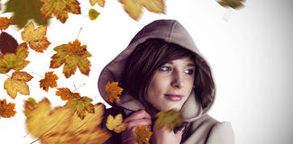 Composite image of beautiful woman wearing winter coat looking away Royalty Free Stock Photo