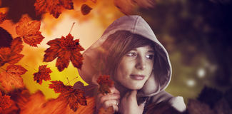 Composite image of beautiful woman wearing winter coat looking away Royalty Free Stock Image