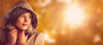 Composite image of beautiful woman wearing winter coat looking away Stock Photos