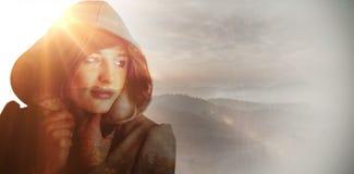 Composite image of beautiful woman wearing winter coat looking away Stock Photo