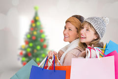 Composite image of beautiful women holding shopping bags looking away Royalty Free Stock Photos