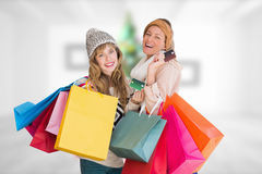 Composite image of beautiful women holding shopping bags looking at camera Royalty Free Stock Photos