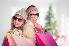 Composite image of beautiful women holding shopping bags looking at camera Stock Image