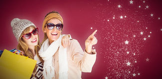 Composite image of beautiful women holding shopping bags pointing Stock Photography