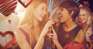 Composite image of beautiful women singing song together. Beautiful women singing song together against love heart pattern Royalty Free Stock Photo