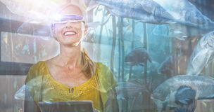 Composite image of big fish swimming in a tank. Big fish swimming in a tank against female business executive in virtual reality video glasses using digital royalty free stock photography