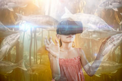 Composite image of big fish swimming in a tank. Big fish swimming in a tank against little girl wearing virtual reality glasses stock images