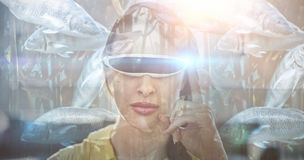 Composite image of big fish swimming in a tank. Big fish swimming in a tank  against  woman wearing virtual reality simulator  Woman wearing virtual reality Stock Photography