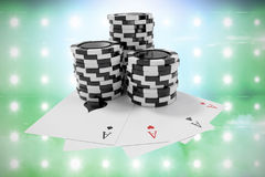 Composite image of black casino tokens with playing cards. Black casino tokens with playing cards against illuminated blue floodlight Royalty Free Stock Photography